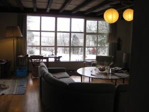 het achterraam met uitzicht naar de wintertuin en de houten balken in het plafond